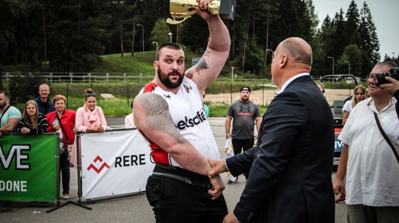 """Čempiona kausu Superfināla uzvarētājam pasniedz aizsardzības ministrs Raimonds Bergmanis Foto: """"Spēka Sporta Centrs"""""""