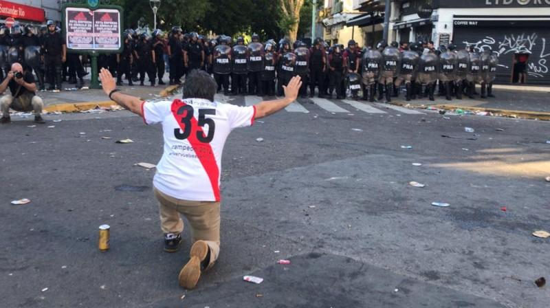 """""""River Plate"""" līdzjutējs policistu priekšā. Foto: AFP/Scanpix"""