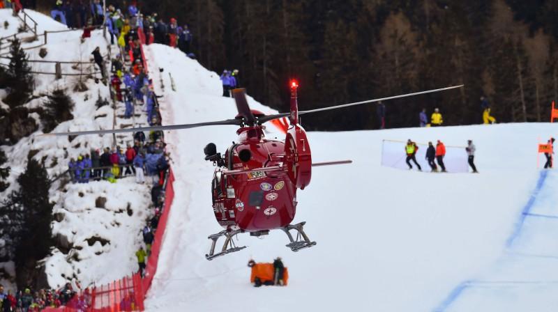Glābšanas helikopters ierodas, lai aprūpētu smagu kritienu piedzīvojušo Marku Gisinu. Foto: AFP/Scanpix