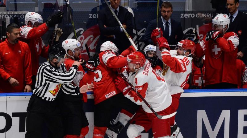 Krievijas un Šveices hokejisti iesaistās asumos pasaules čempionāta spēlē. Foto: AFP/Scanpix